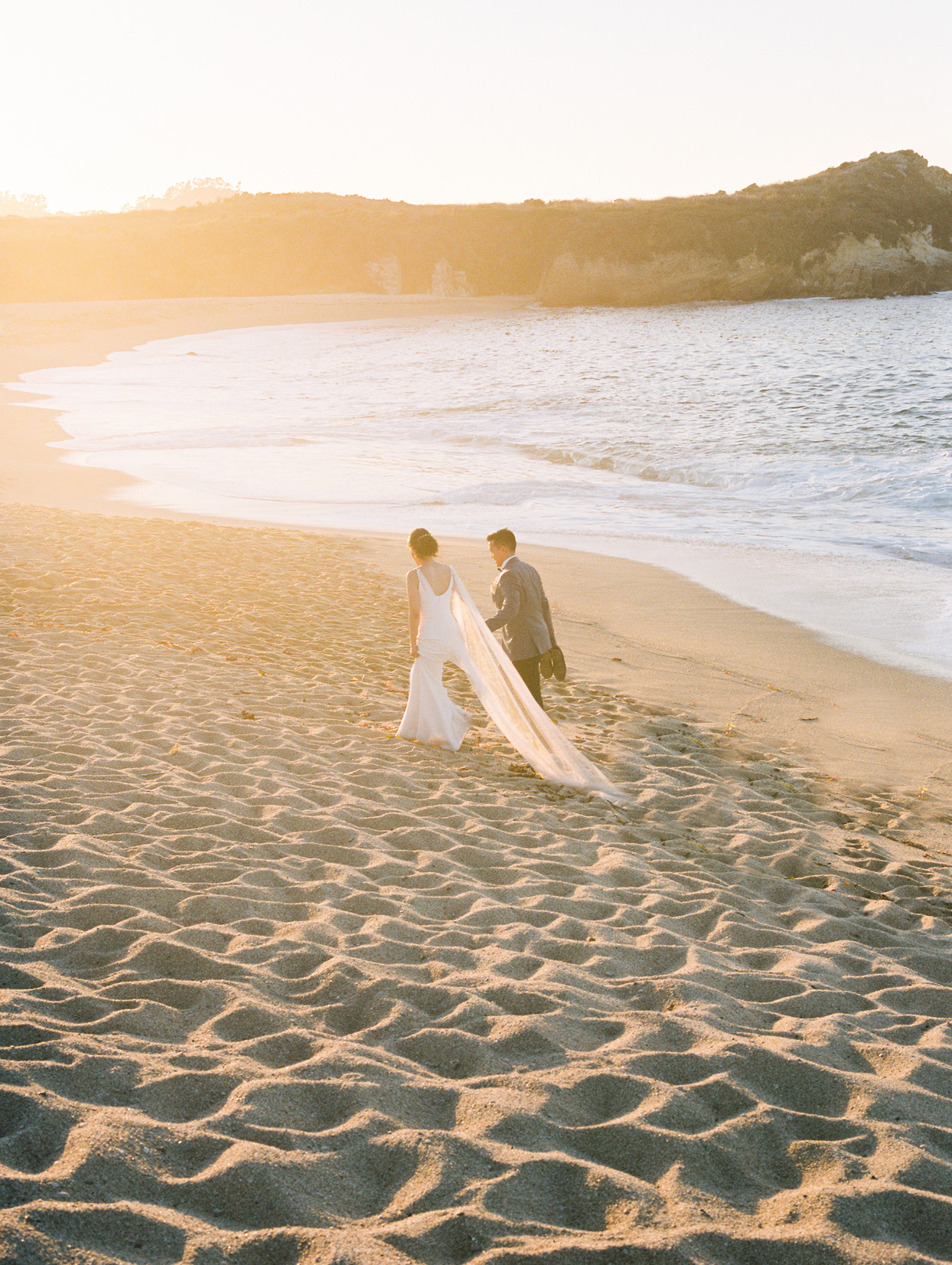 bride and groom walking hand in hand on beach