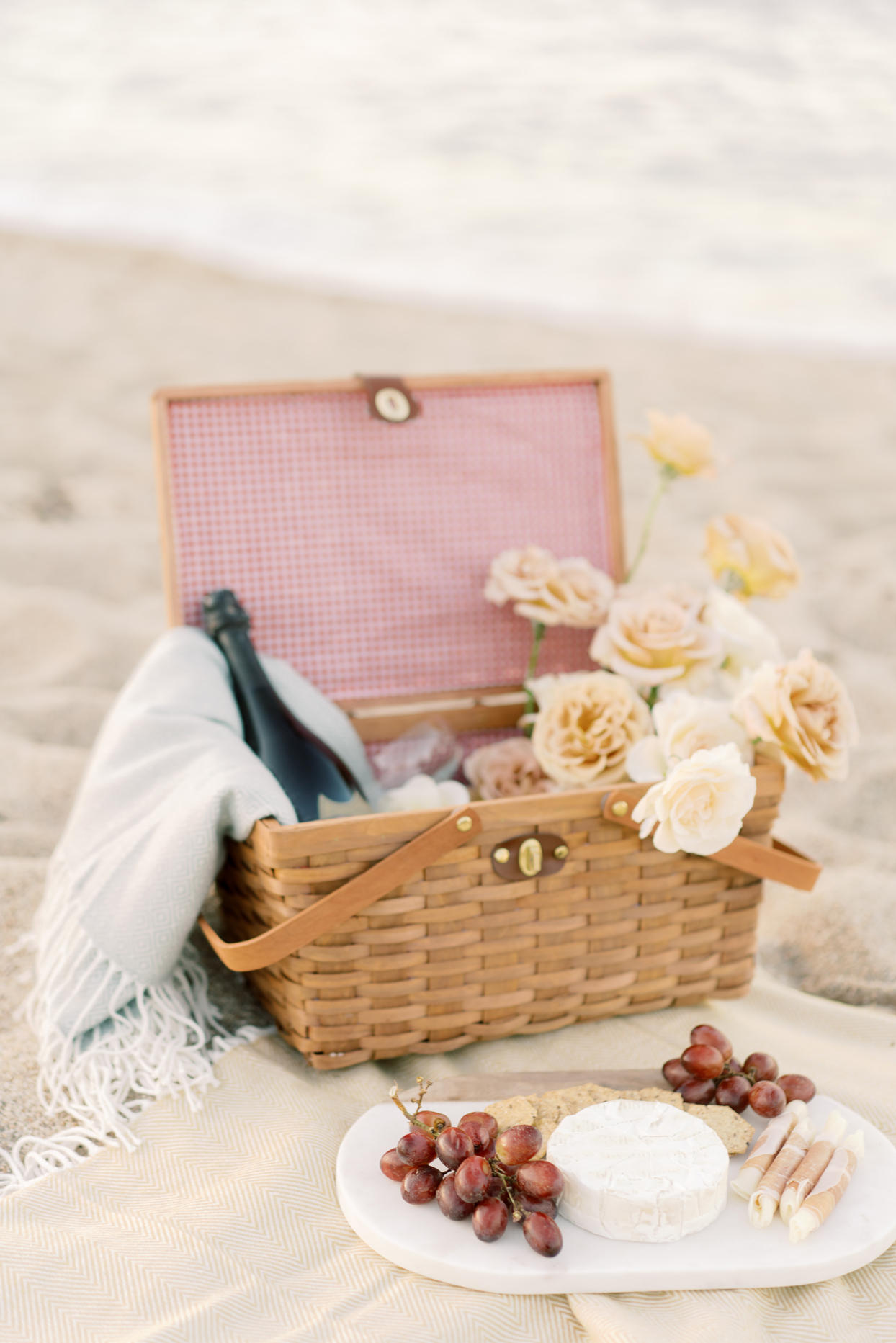 picnic basket with blanket and cheese board