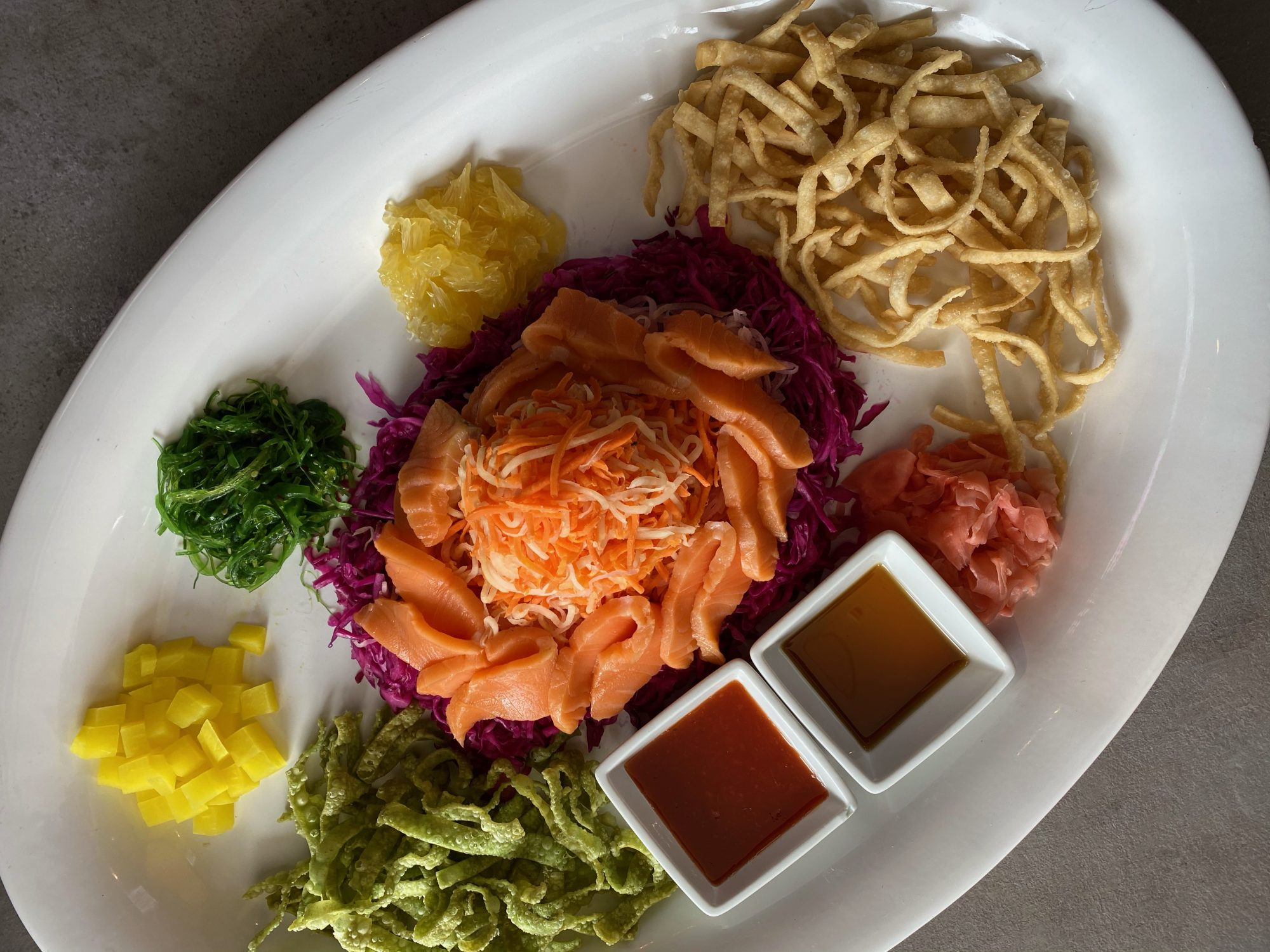 prosperity toss with raw salmon, pickled vegetables, and wontons from Phat Eatery restaurant