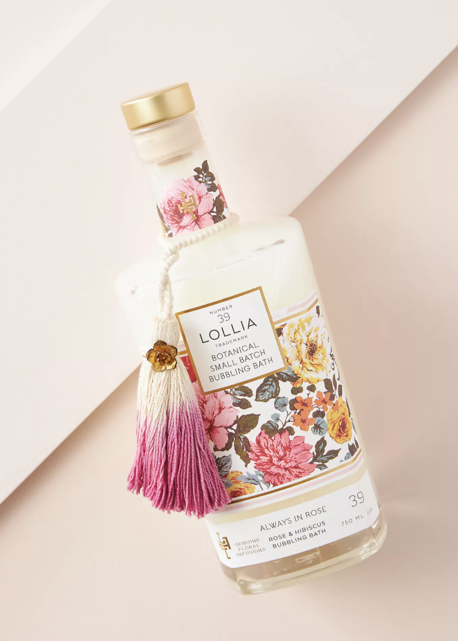 bubble bath in floral bottle with pink and white tassel in front of a blush background