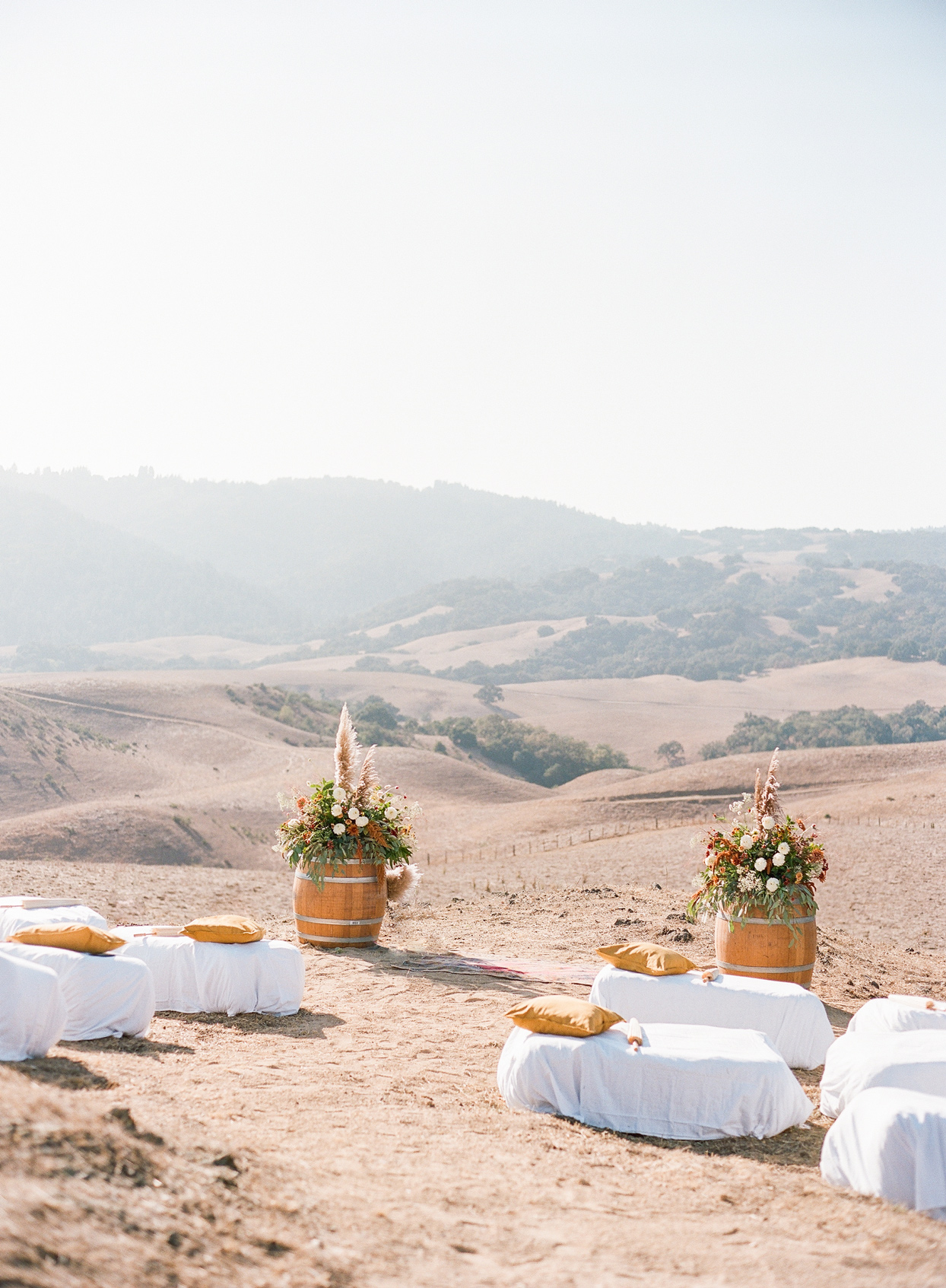 ceremony set up with pillow seating and floral arrangements