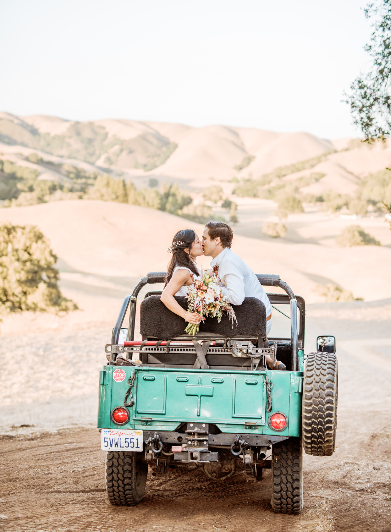 bride and groom in teal-colored Jeep