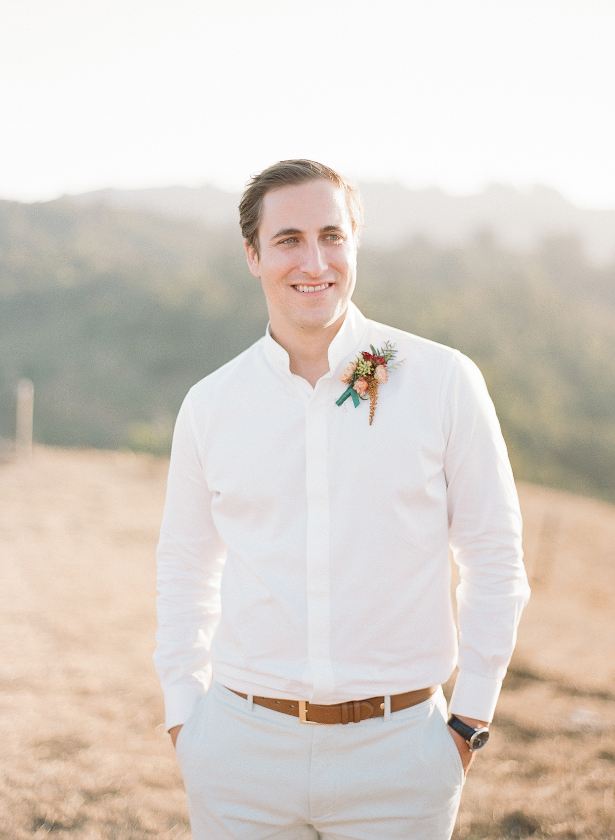 groom in white button up and light colored shorts