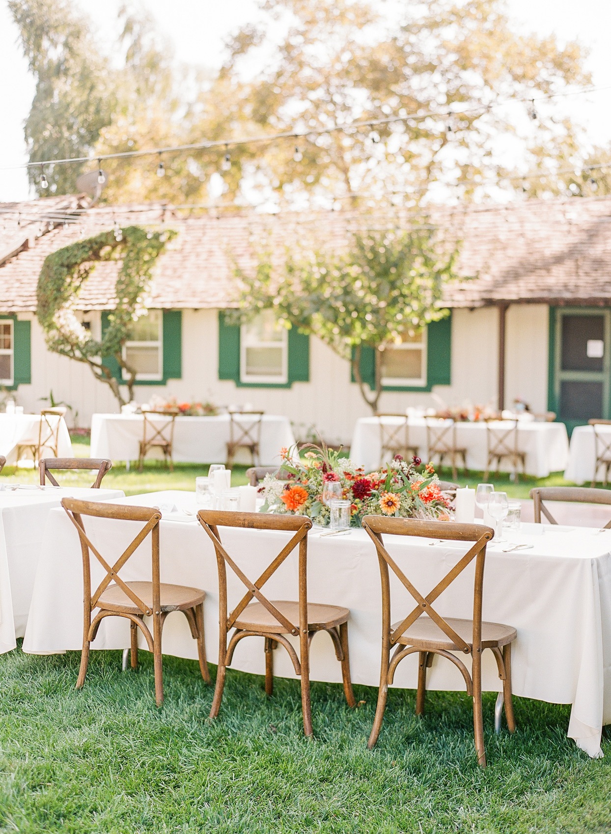 Long guest tables with white linens and florals