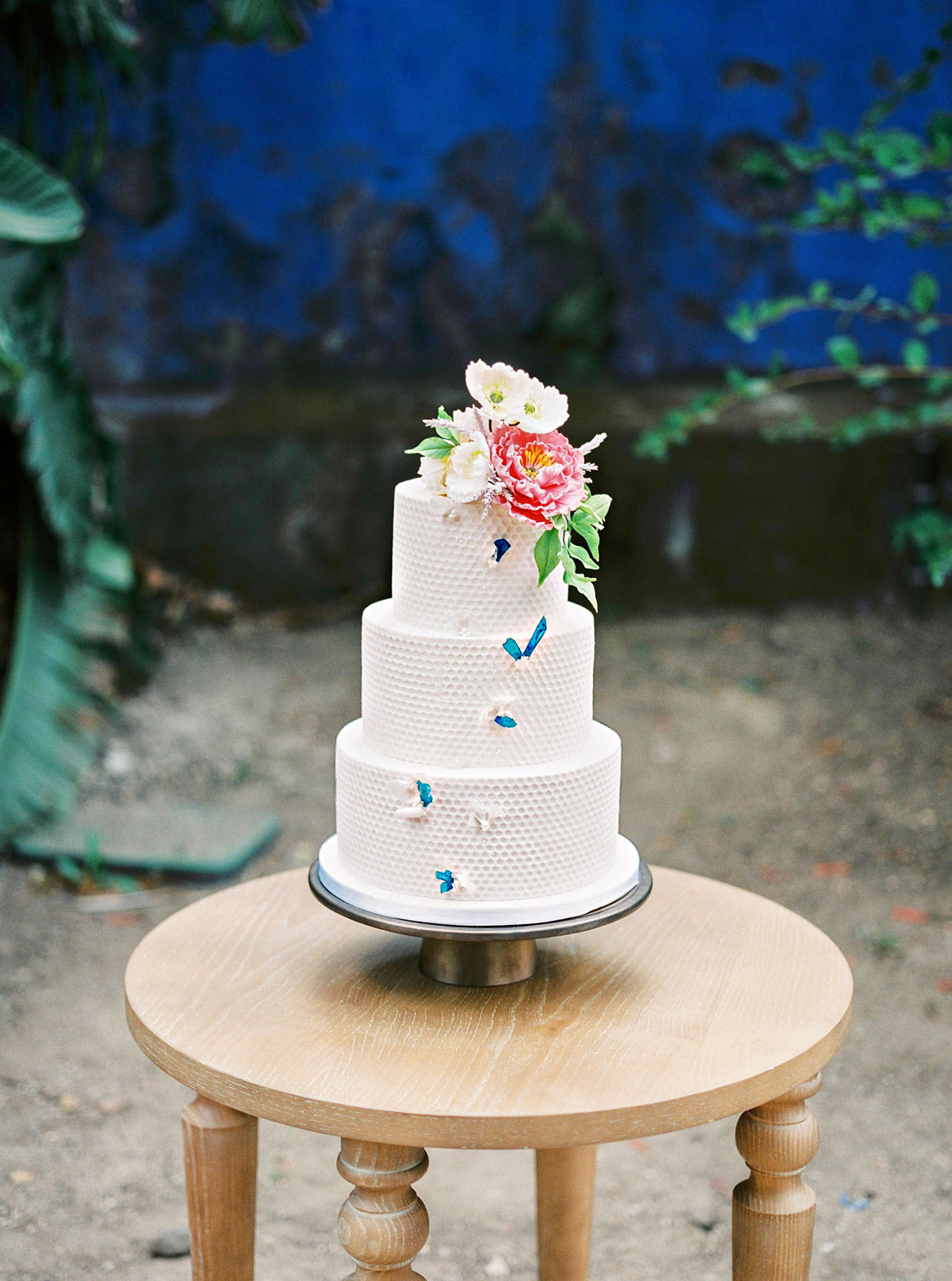 white three-tiered wedding cake with floral topper