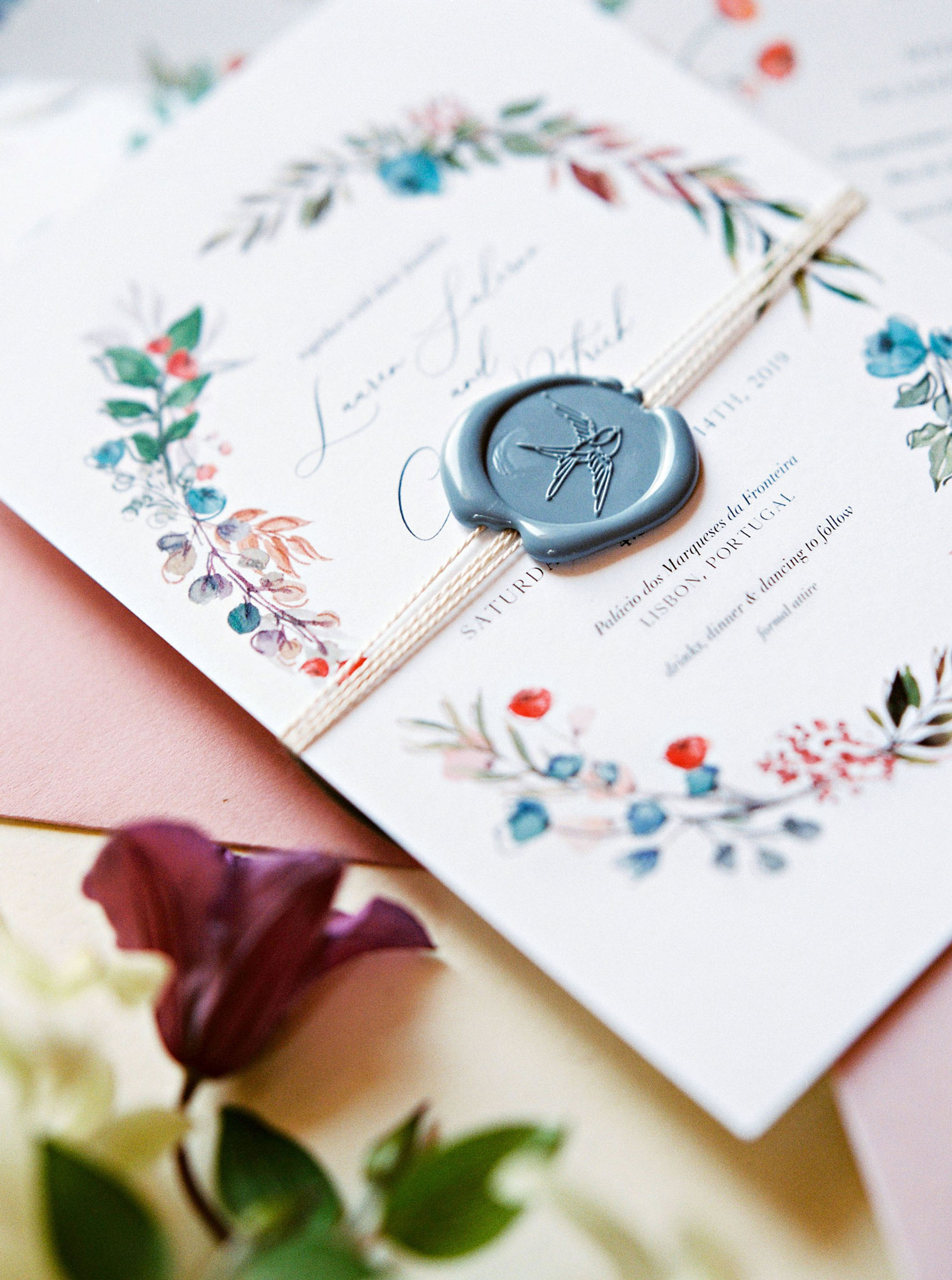 close-up of white wedding invitation with blue stamped wax seal