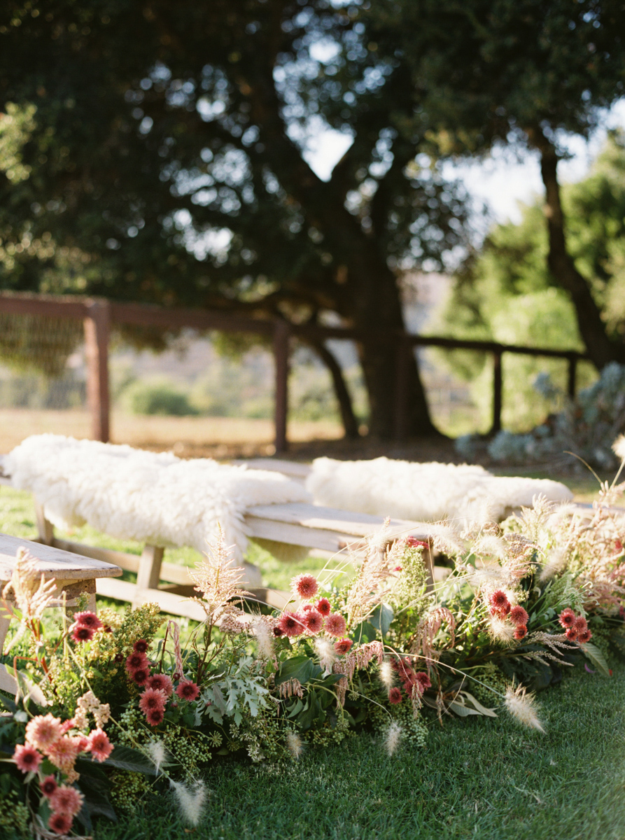 wooden wedding benches with furs and flowers