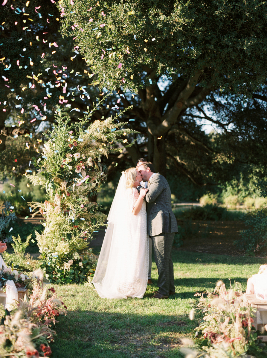 couple kissing during wedding ceremony showered in confetti