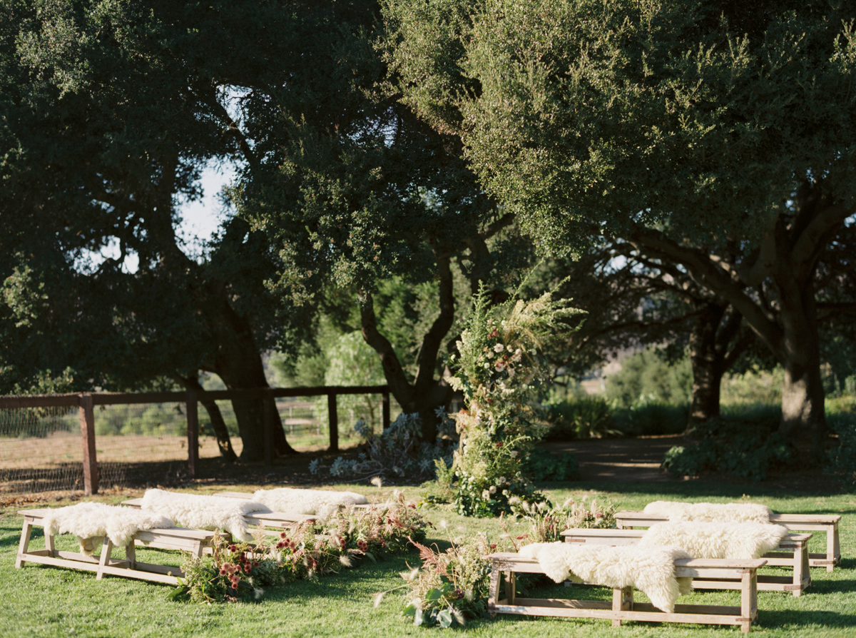 outdoor wedding ceremony with wooden benches and florals