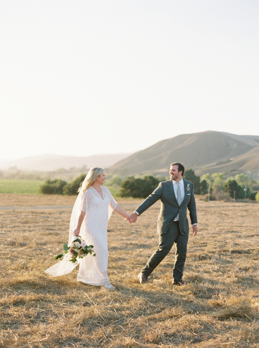 wedding couple holding hands walking through field with hills in background