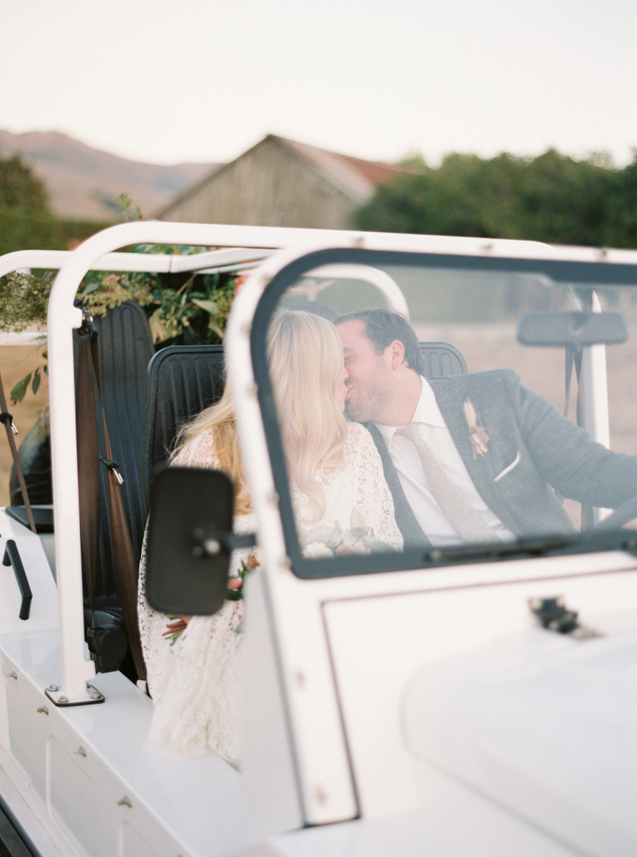 wedding couple kissing in white suv