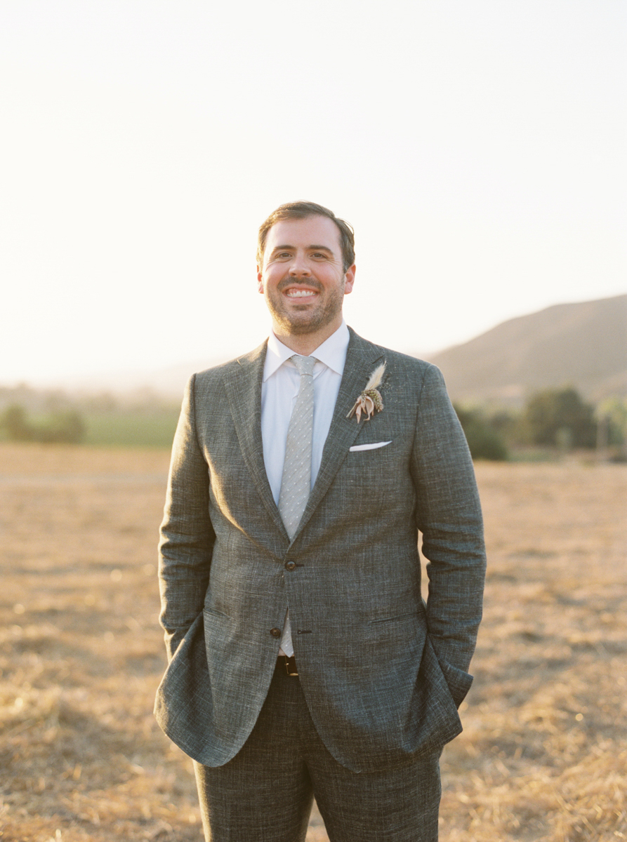 groom in gray suit with wildflower boutonniere