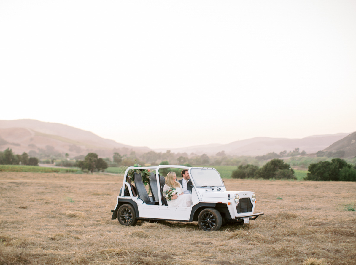 couple driving through field in white jeep