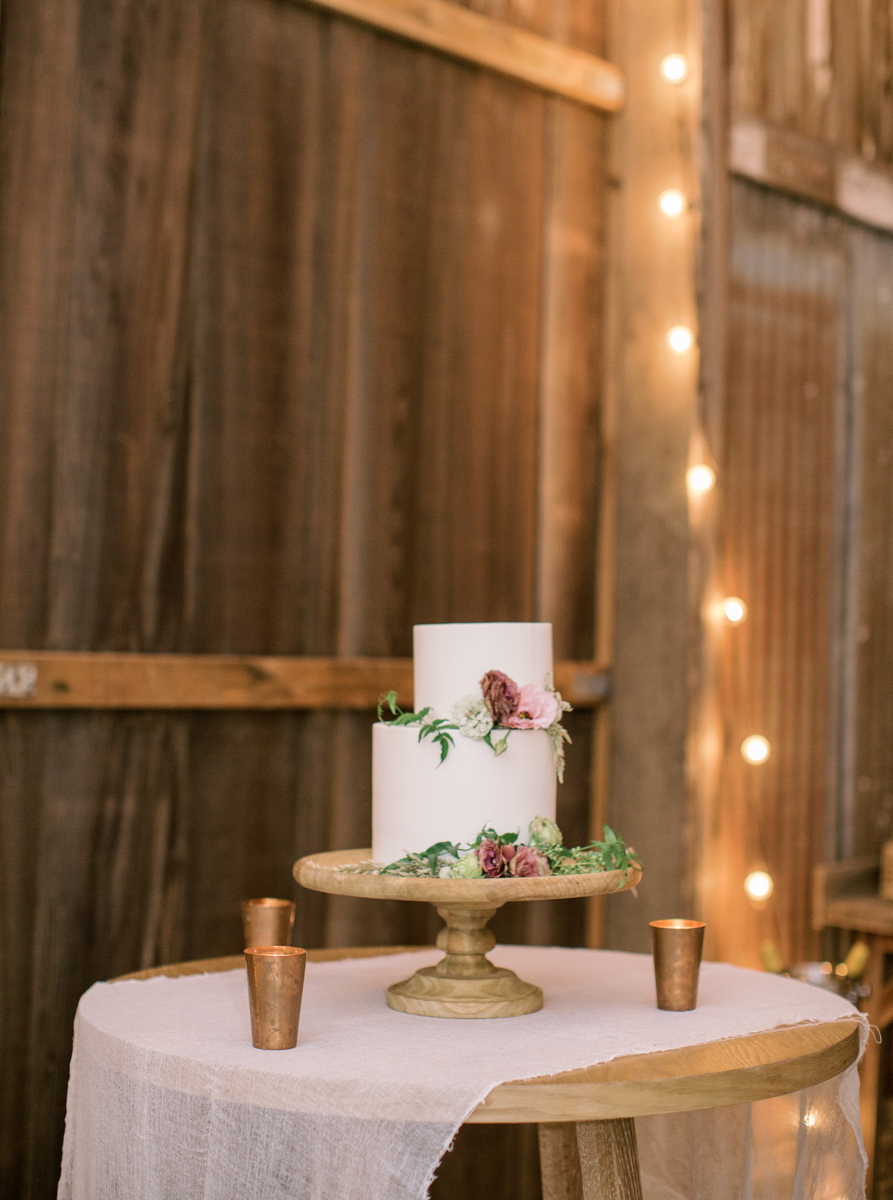 small reception cake in lit barn with flowers