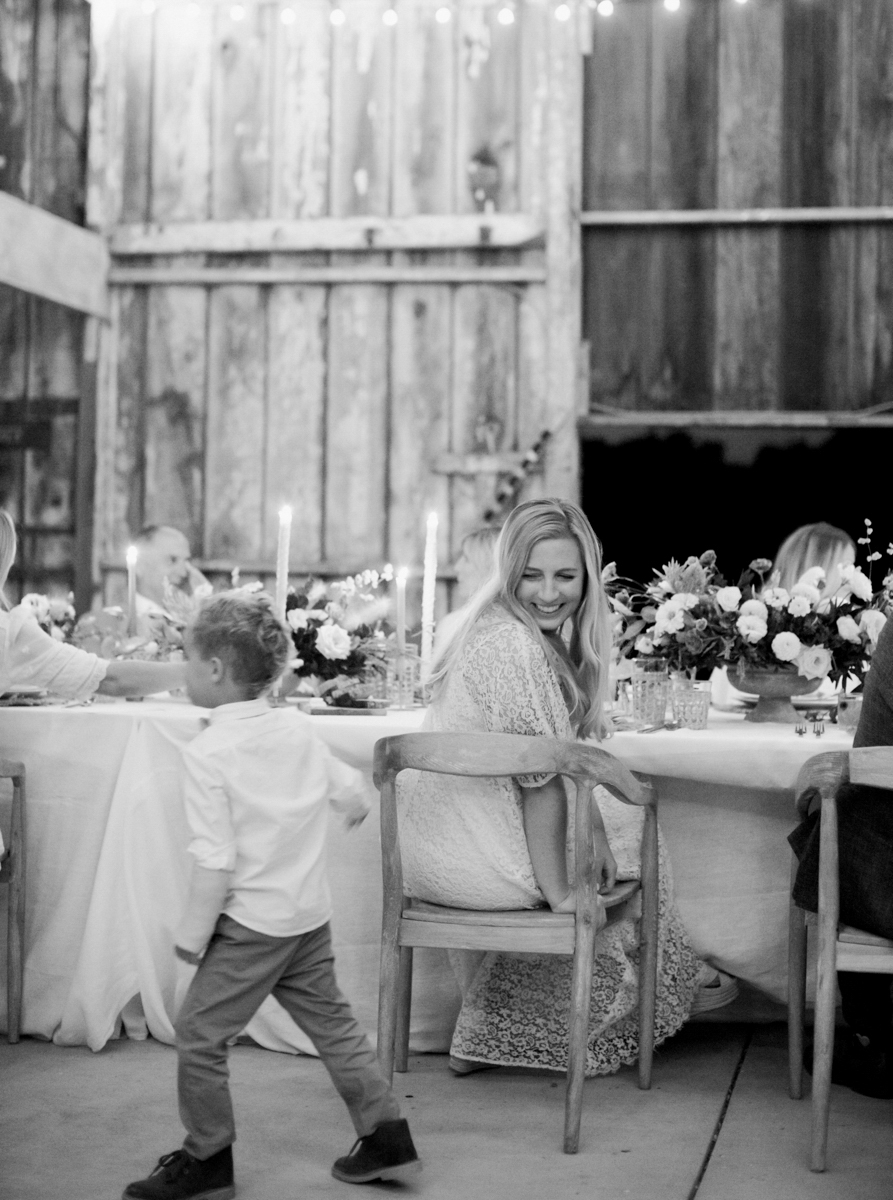 bride sitting at reception table and smiling at little boy running around