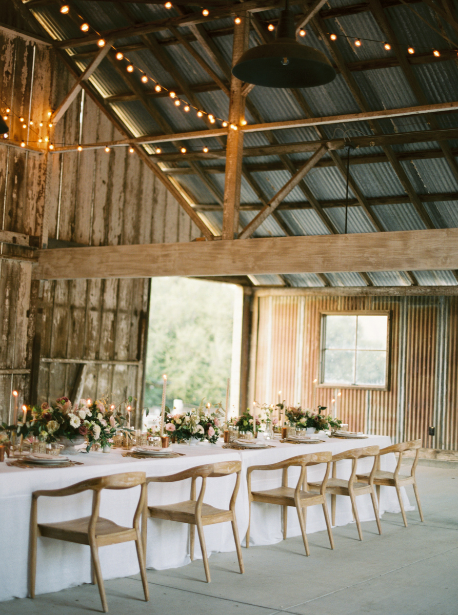 elevated barn reception with long white table, florals and candles