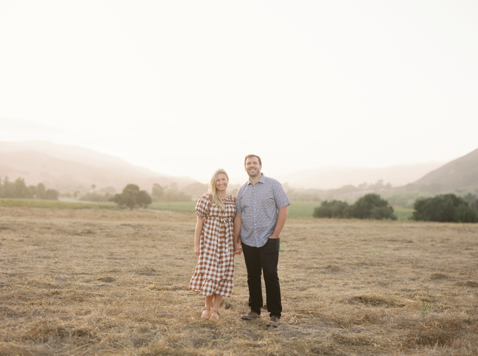 bride in gingham dress and groom holding hands in field
