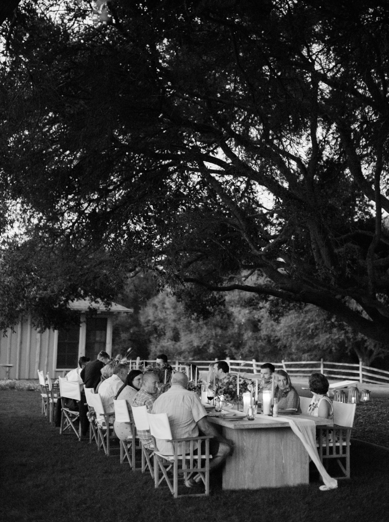 family sitting at wooden table under trees for rehearsal dinner
