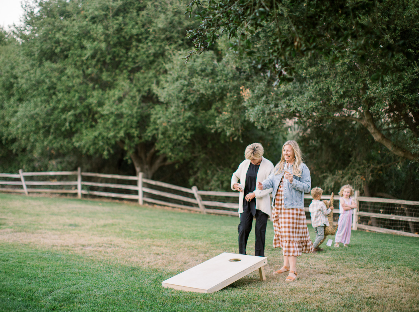 bride and guests playing corn hole at rehearsal dinner