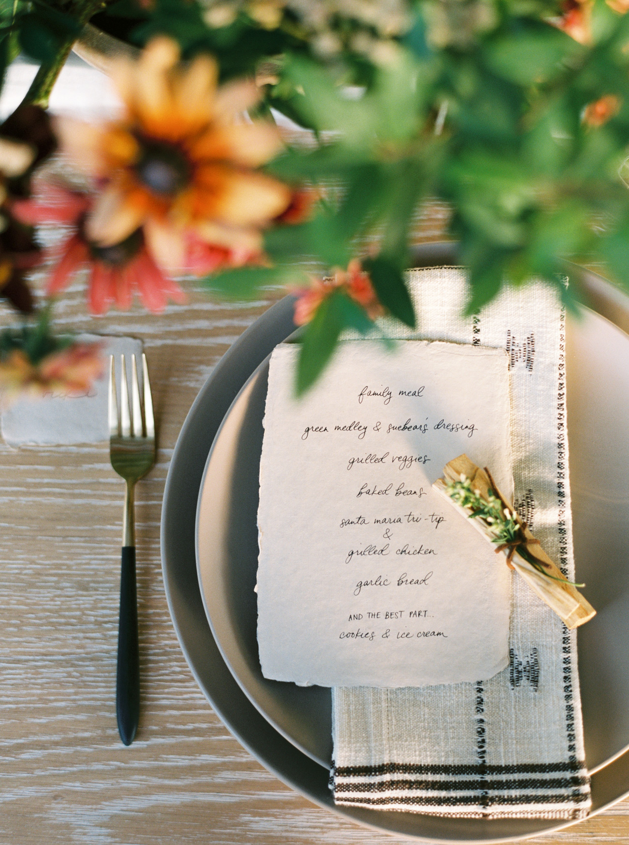 rehearsal dinner place setting with rough edge menu and wild flowers