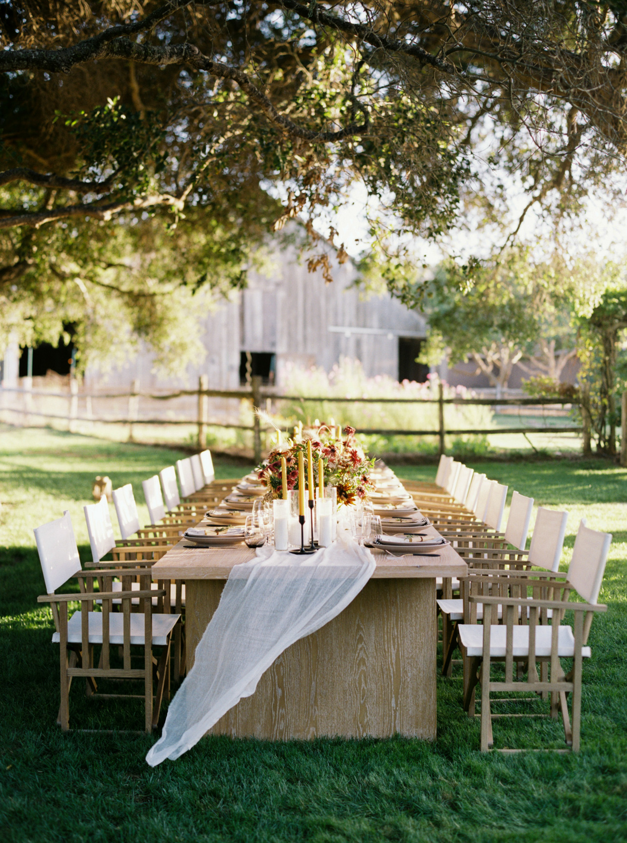 long wooden table set up in grass for rehearsal dinner