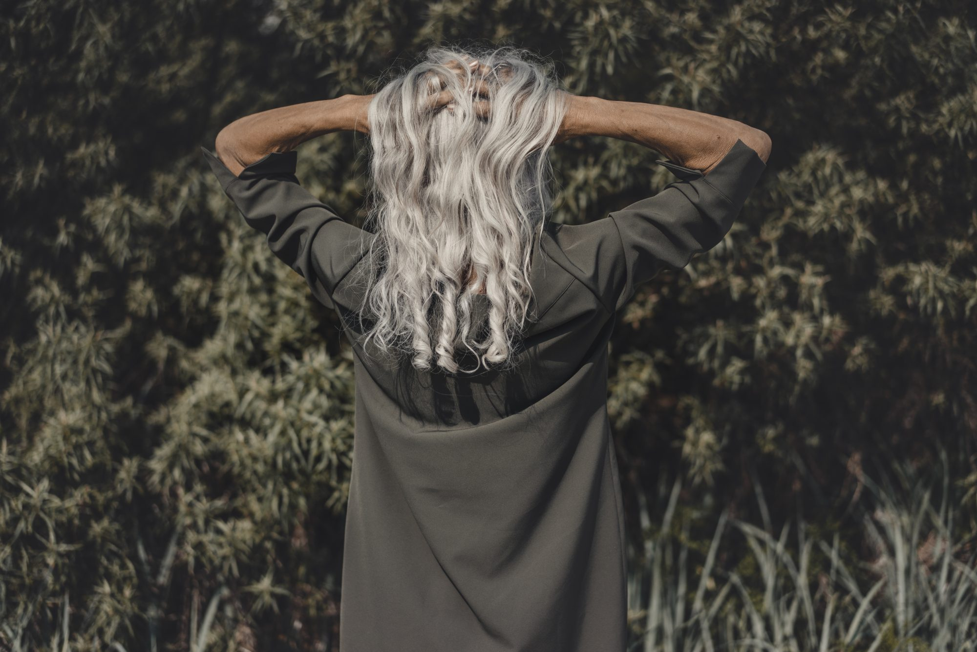 Rear view of senior woman with hands in her white hair
