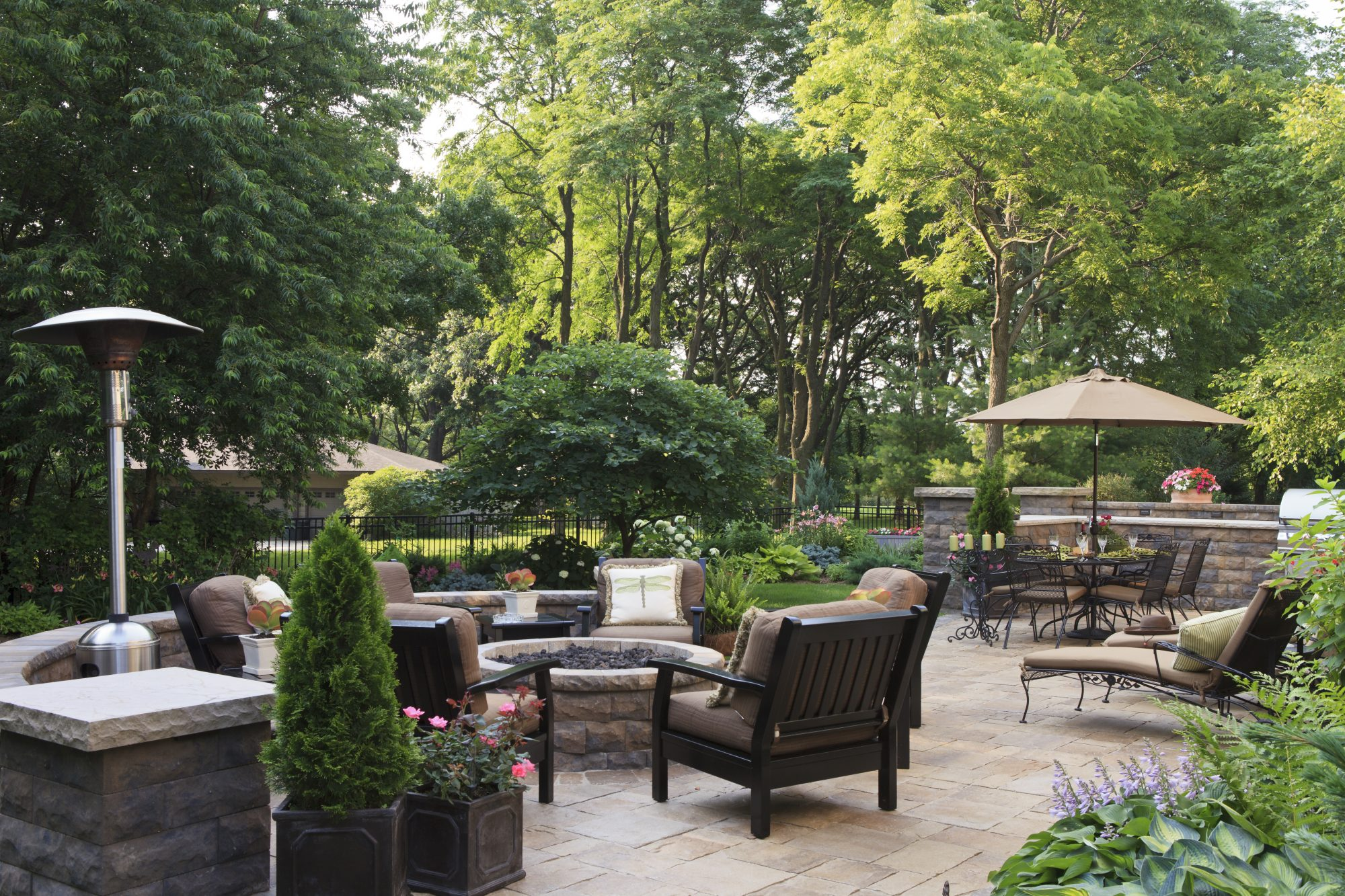 garden patio with firepit, heaters, and seating area