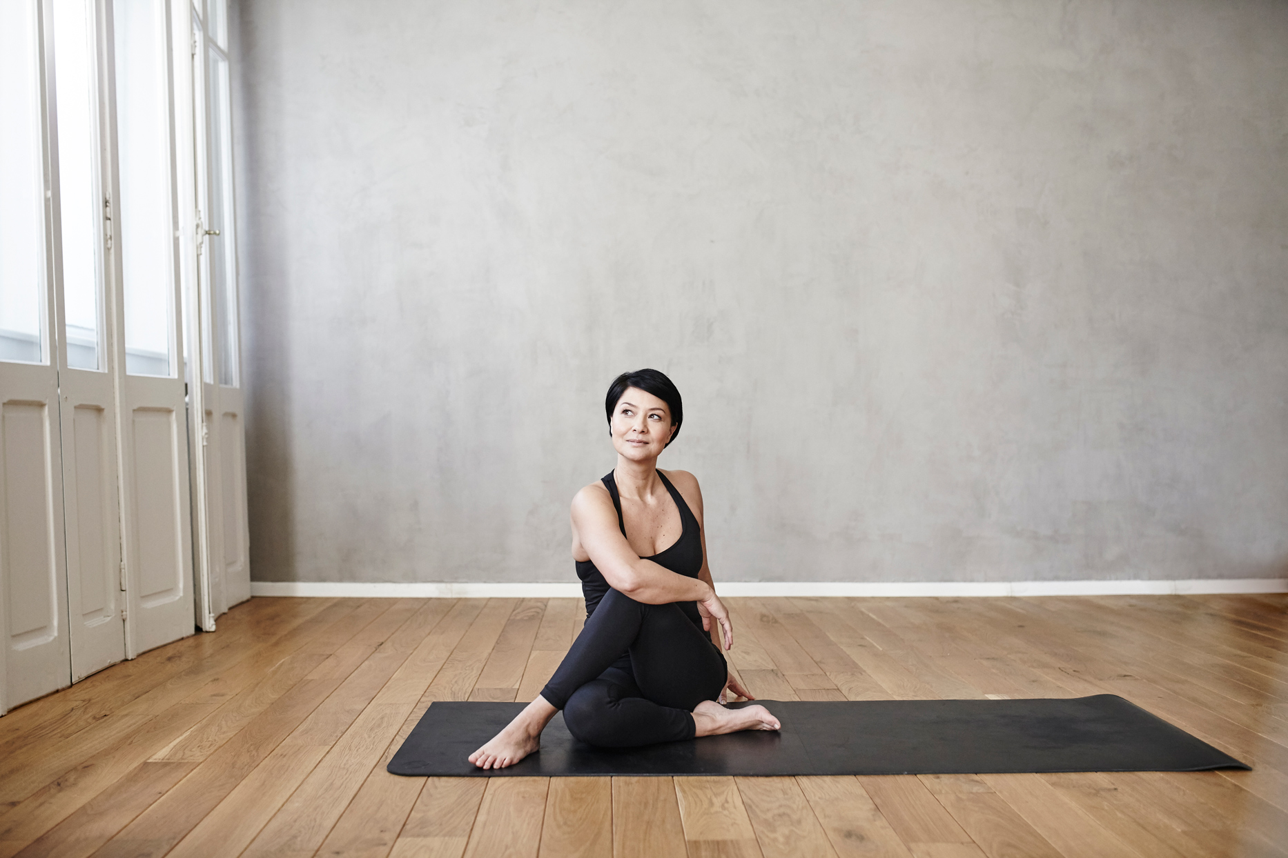 woman in studio room stretching on a yoga mat