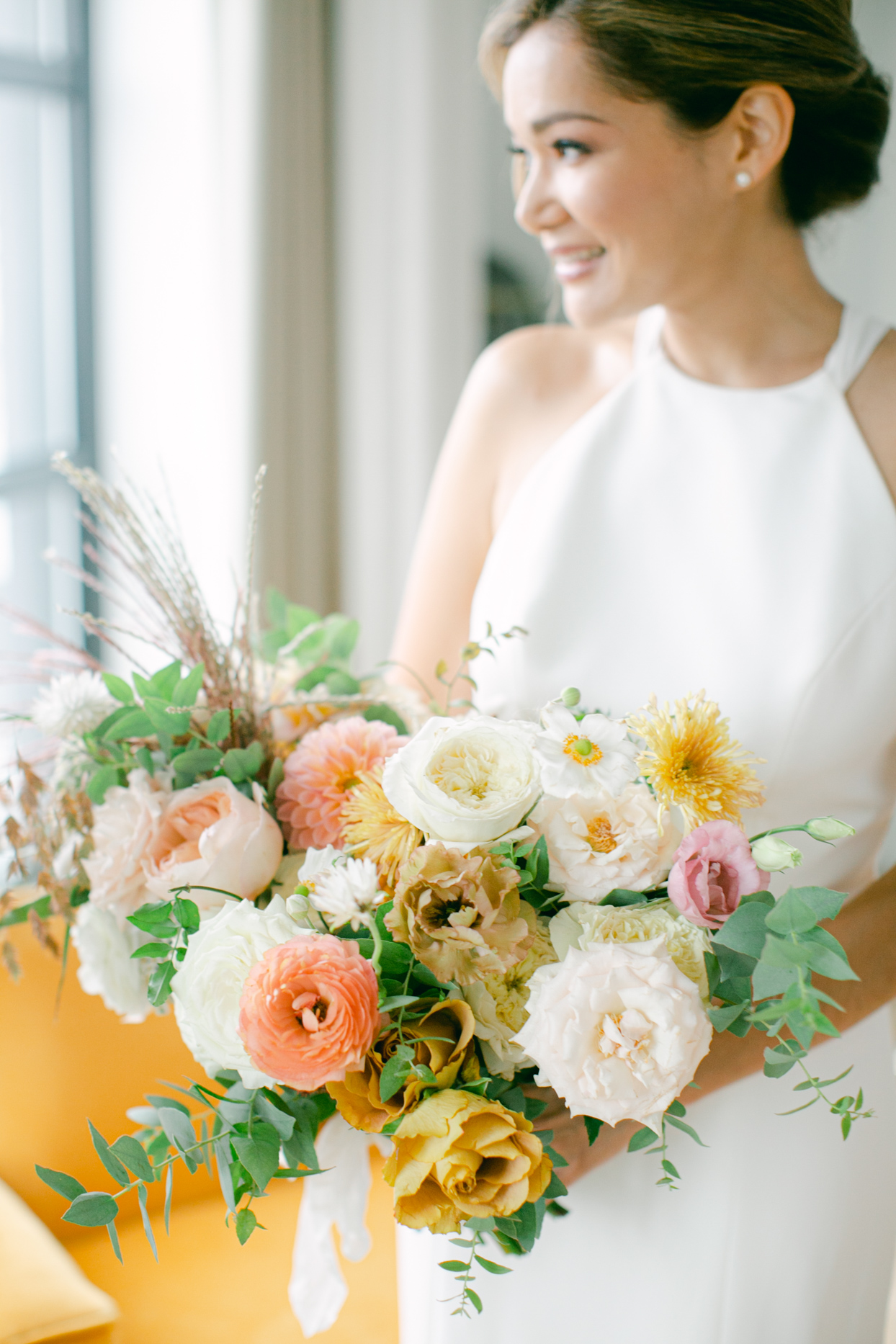 bride holding elegant peach, yellow, and pink bouquet