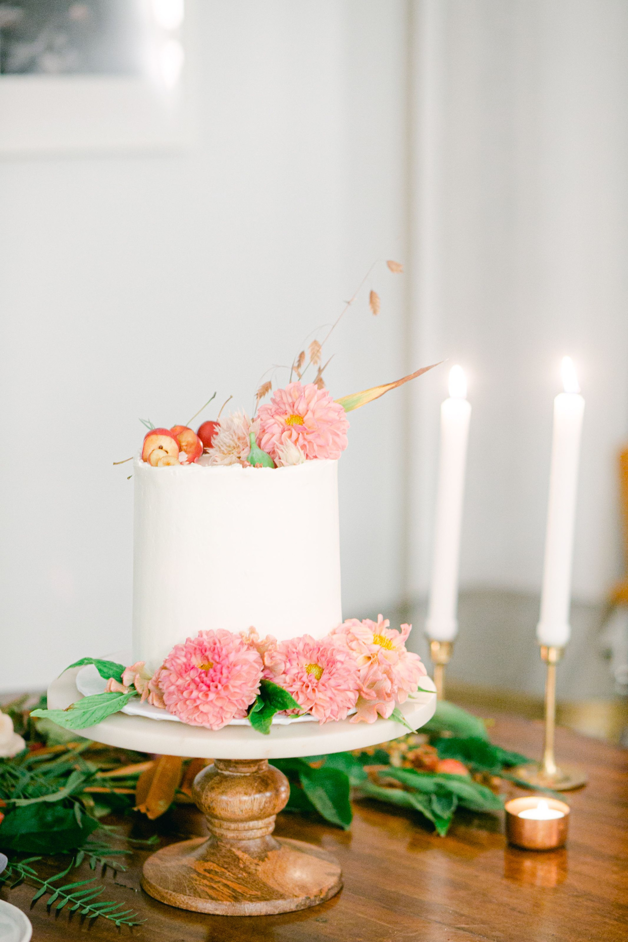 simple single tier wedding cake with pink flowers and candles on table