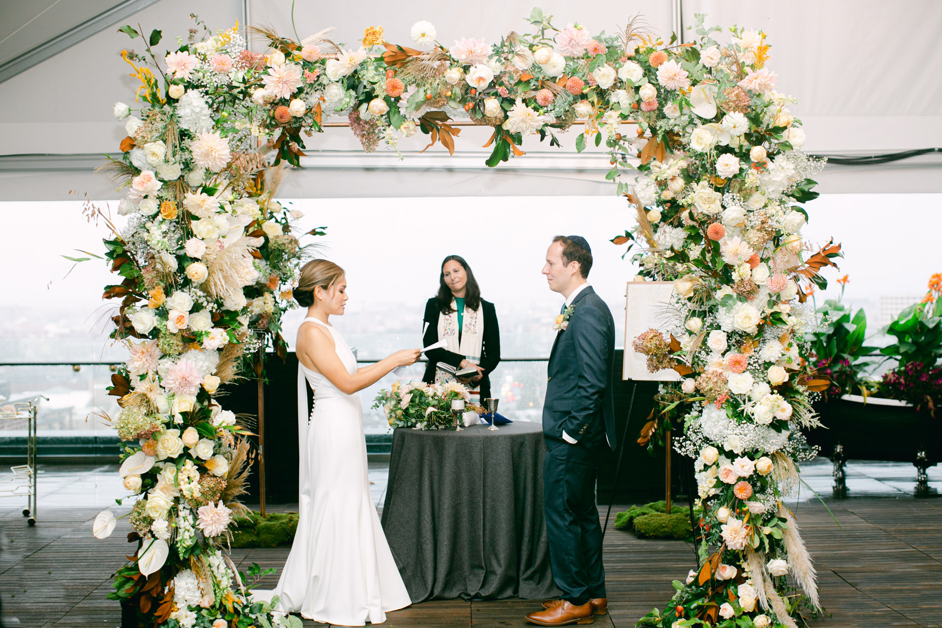 bride and groom changing vows under floral arch