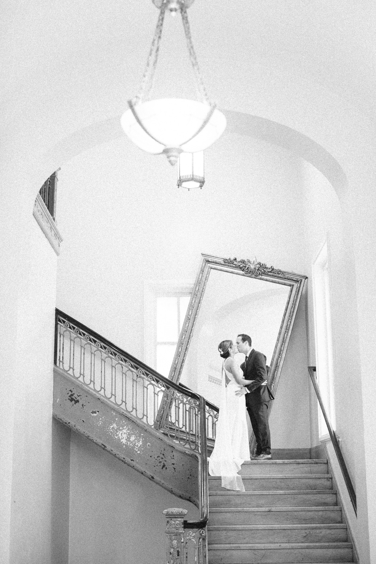 wedding couple kissing on stair with angled mirror behind them