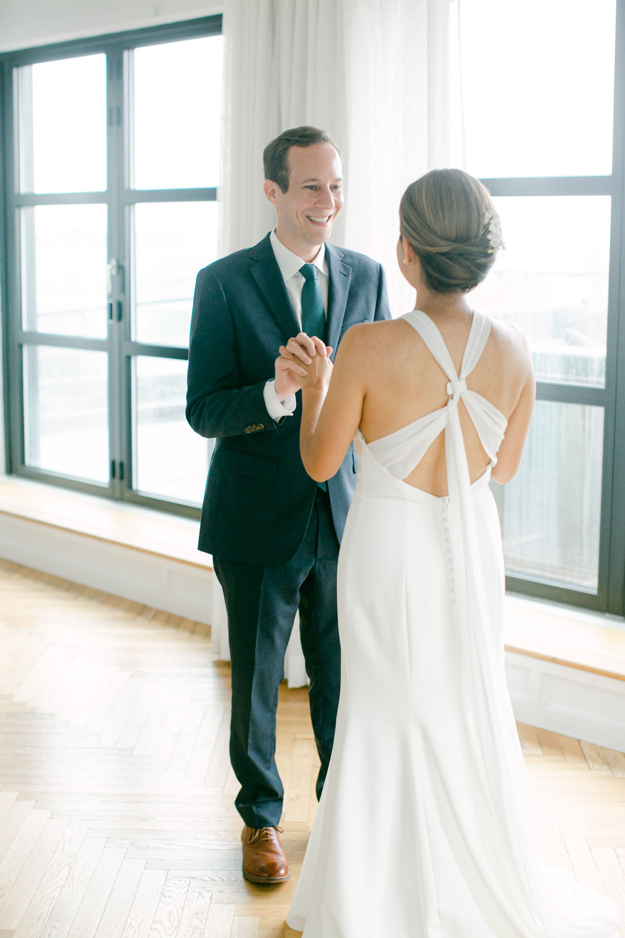 couple smiling and holding hands for first look