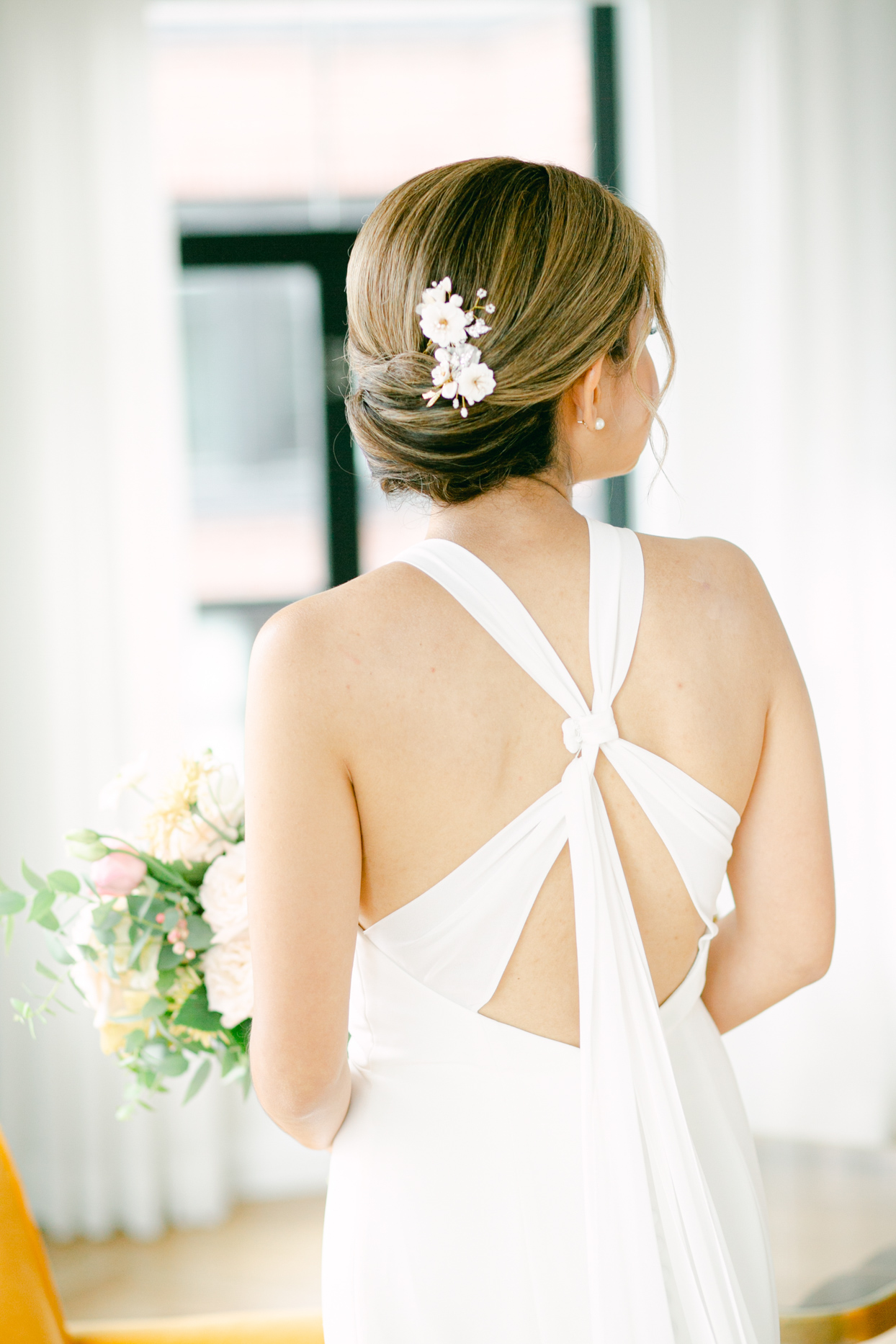 bride's wedding updo with small white floral decoration