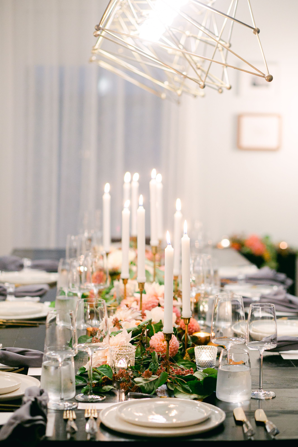 close up of long wedding table with peach florals and candles
