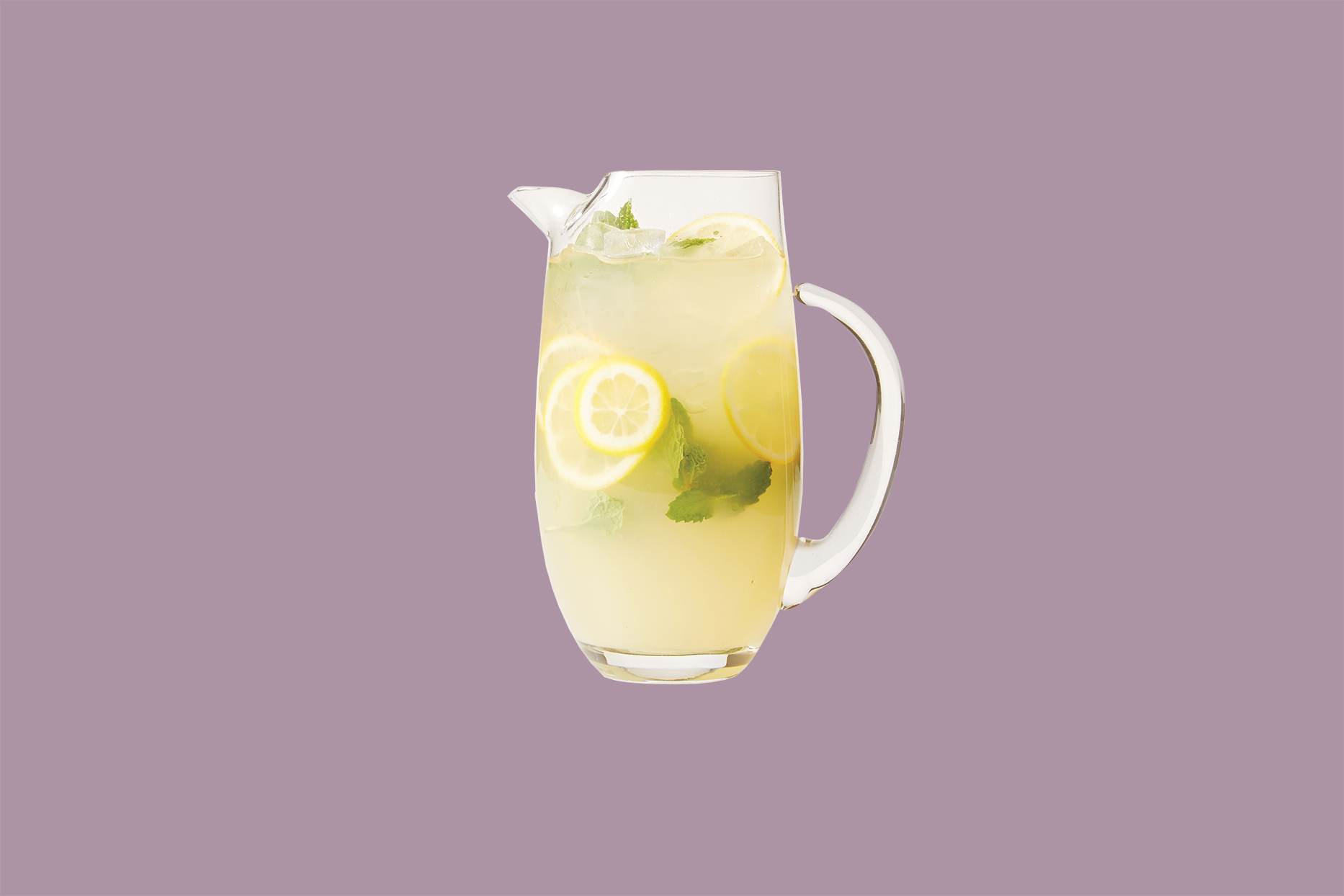 glass pitcher of lemonade with mint leaves and sliced lemons