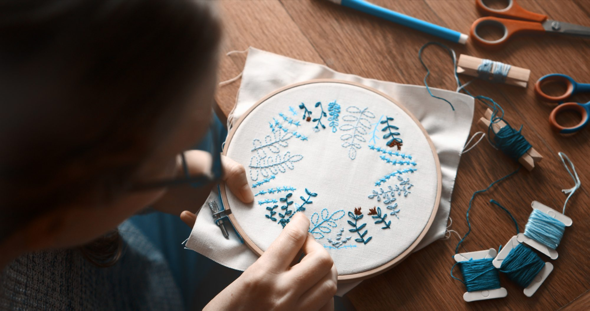 woman doing embroidery at home