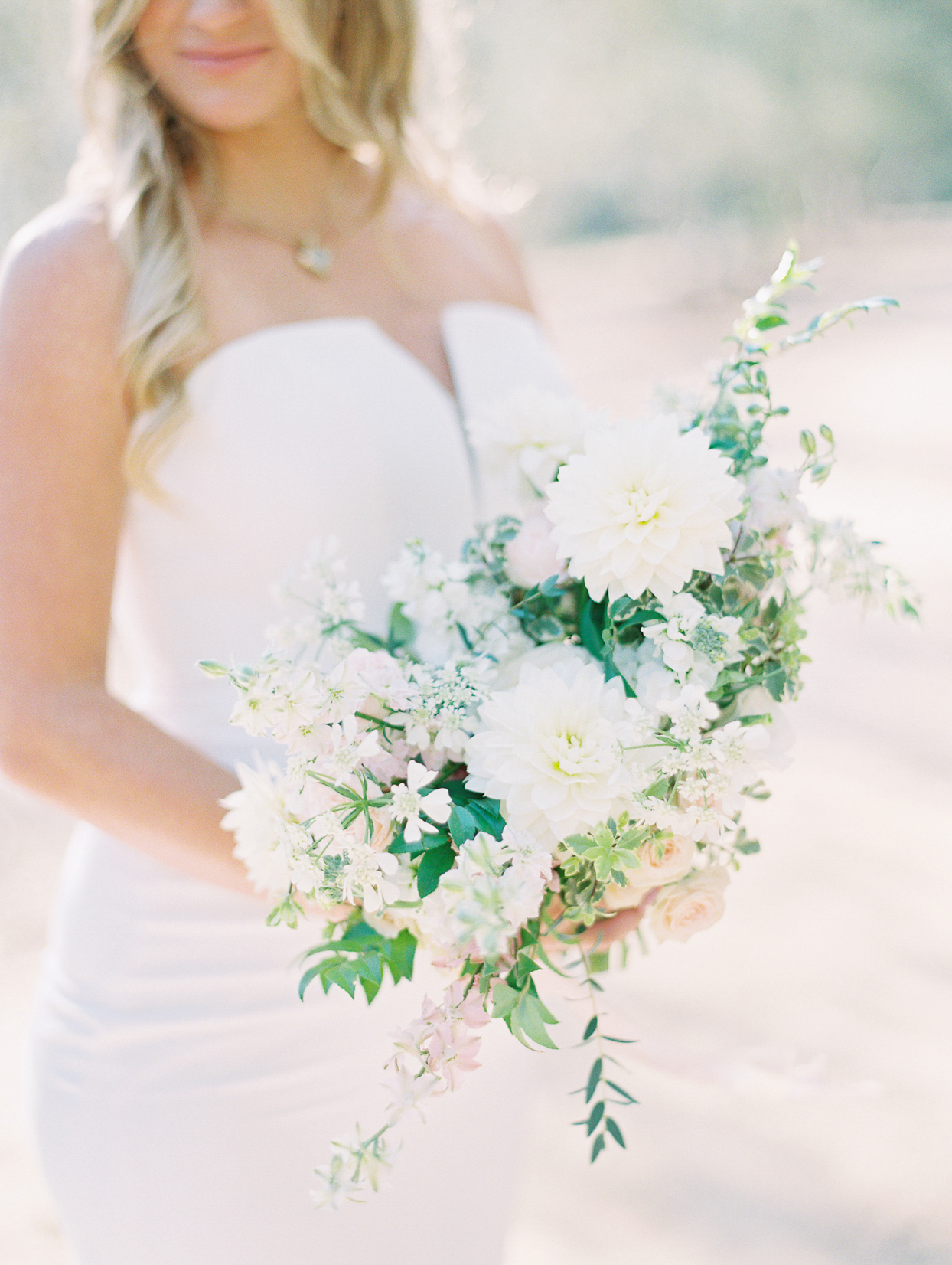 bride holding white and green floral wedding bouquet
