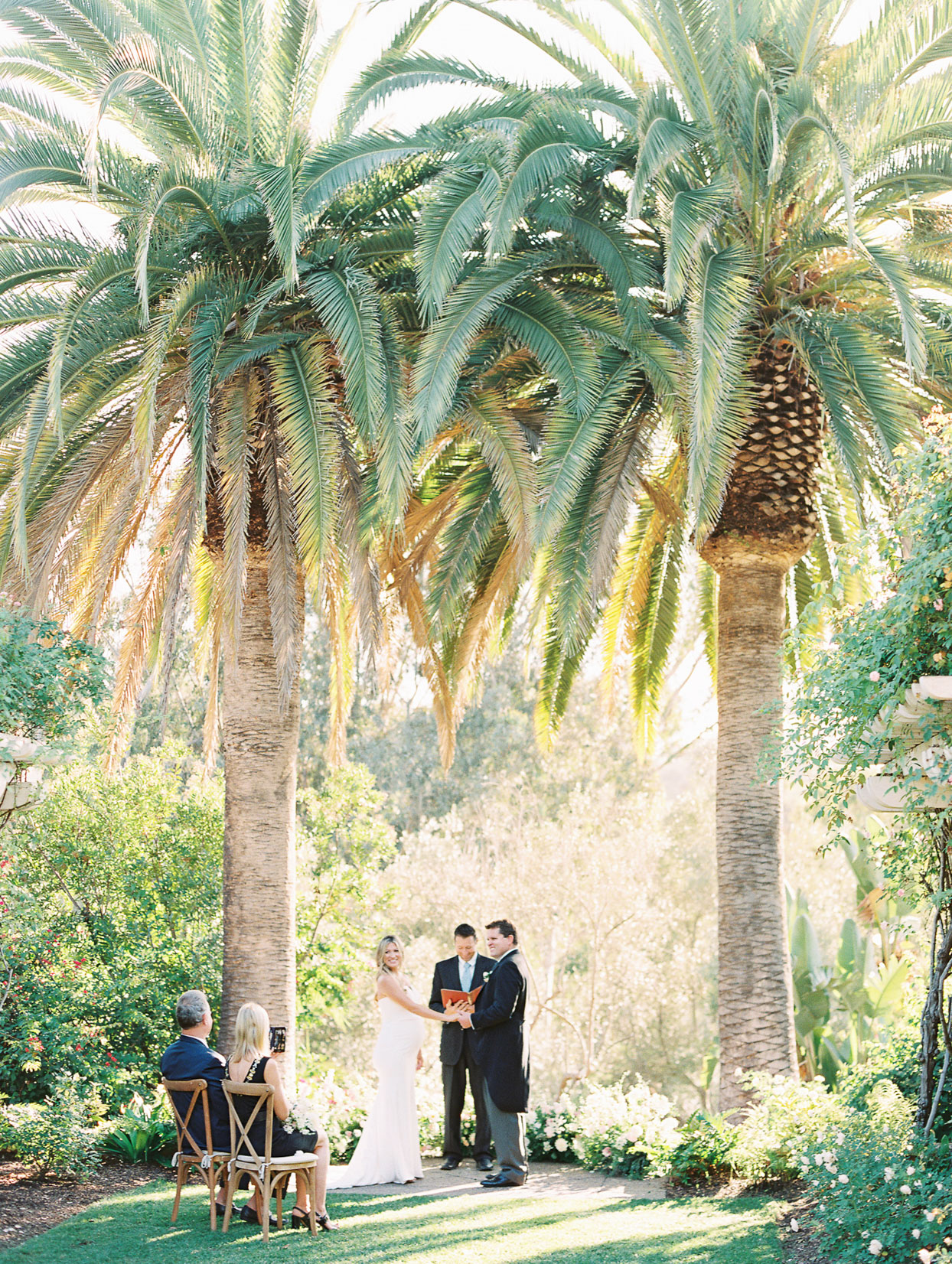 wedding couple holding hands during ceremony under palm trees
