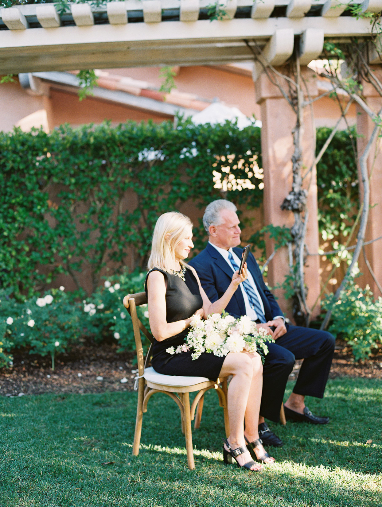 two wedding ceremony guests on wooden chairs