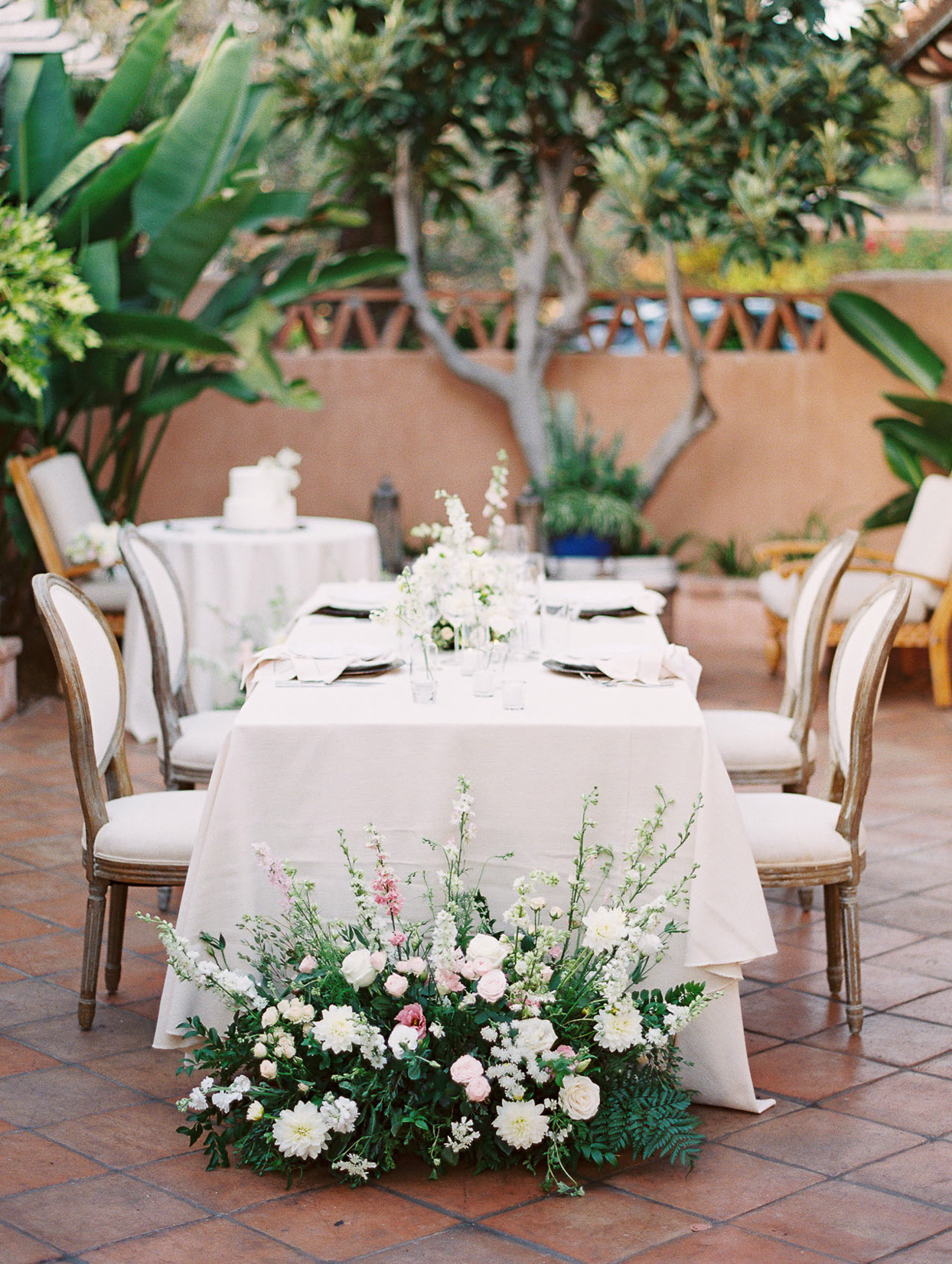 small white table for four on patio for wedding reception
