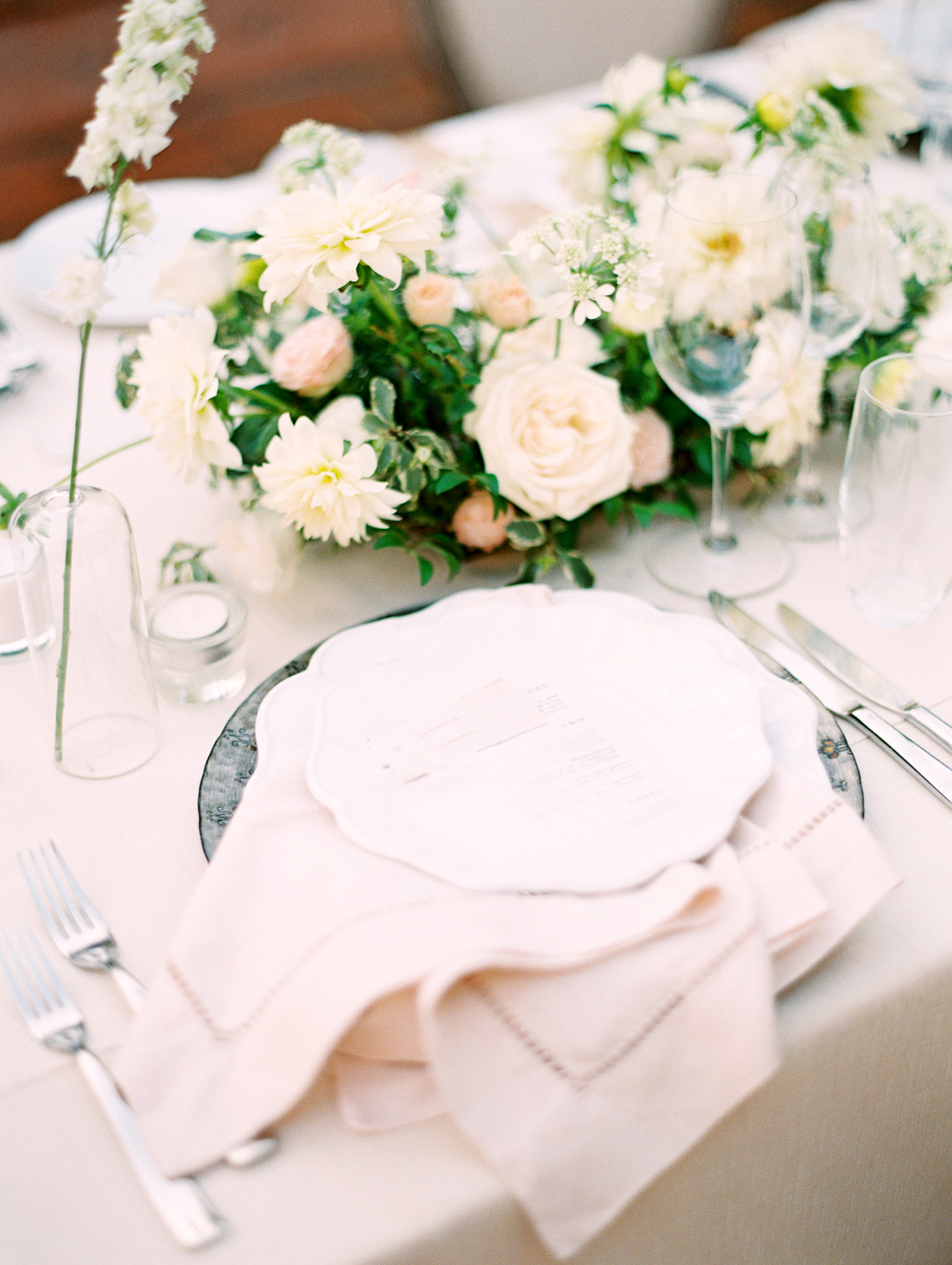 wedding reception white place setting with low florals