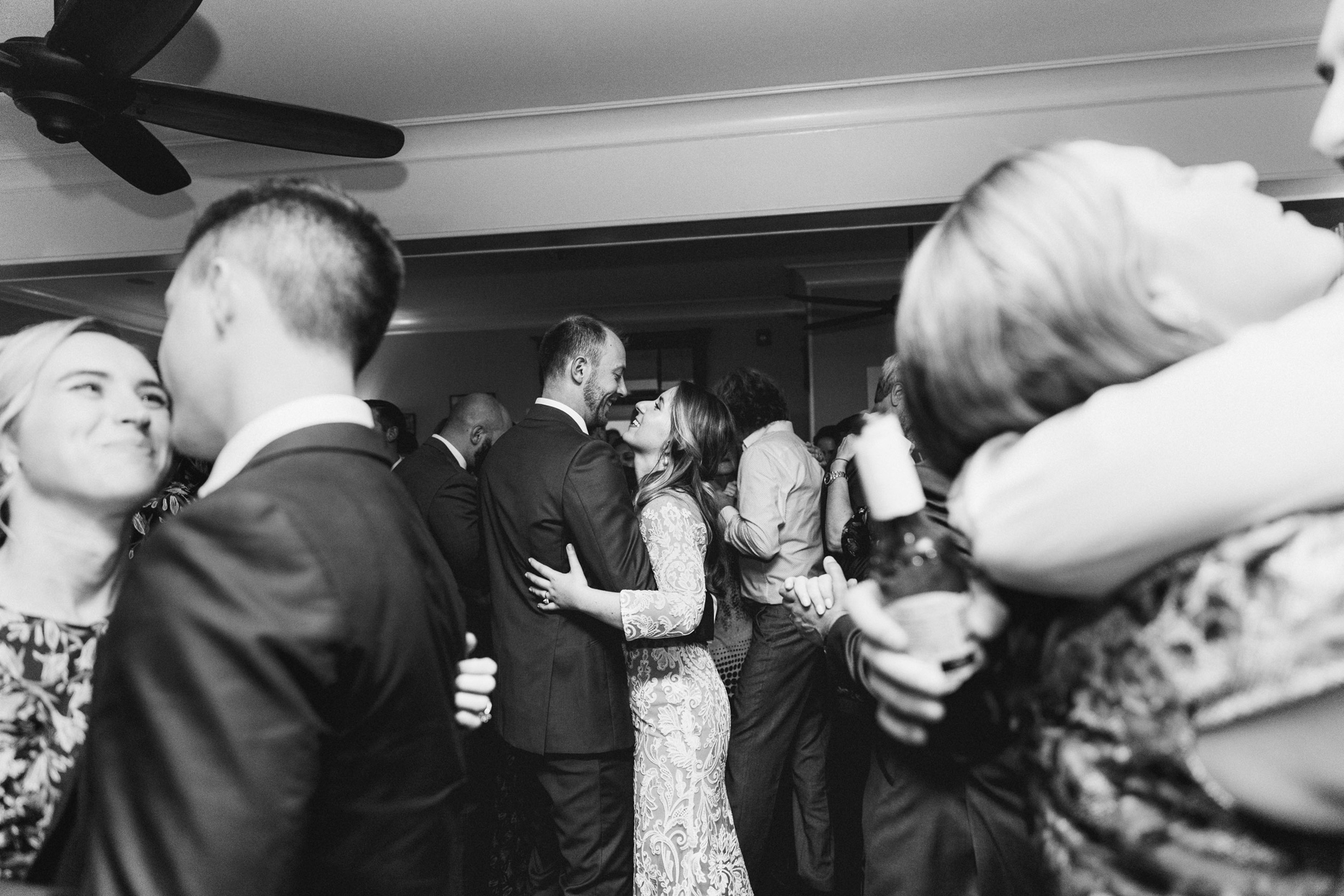 bride and groom dancing at reception with guests around them