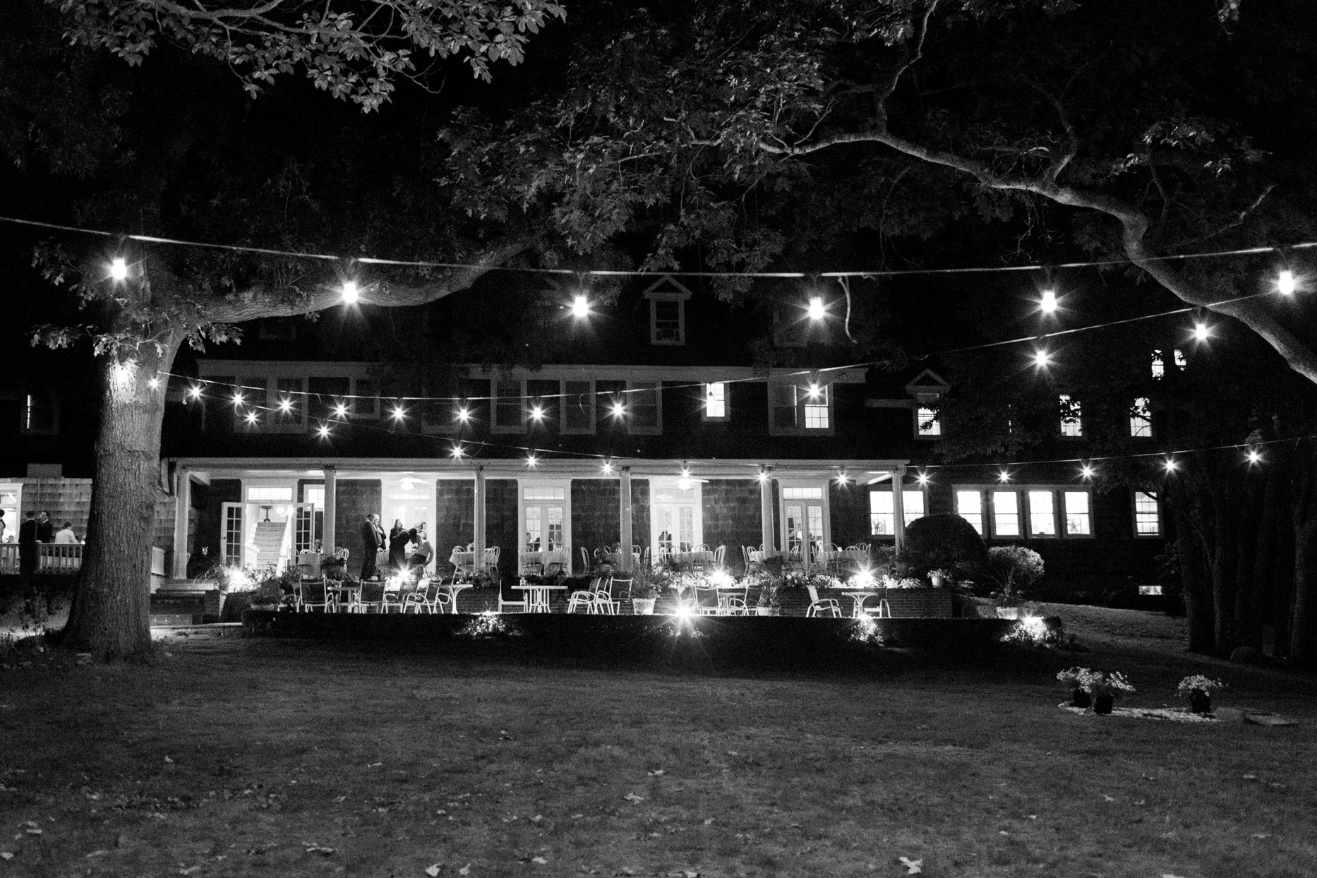 wedding reception seating lit up with string lights outside of house