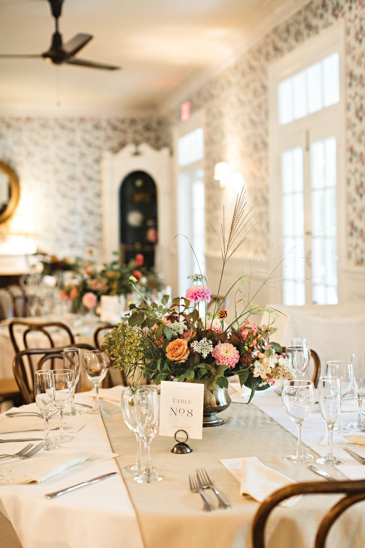 elegant warm reception table set with elevated wildflower bouquet