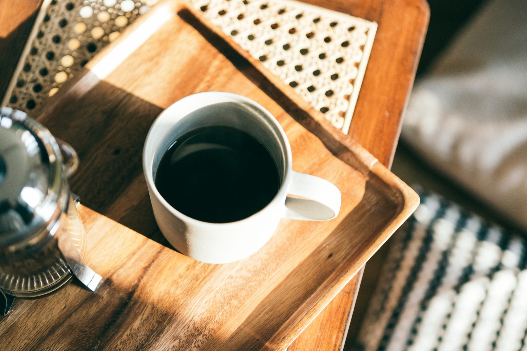 white coffee cup on wood serving tray