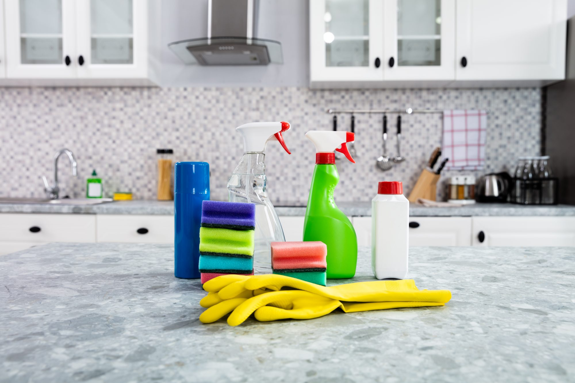 assortment of cleaning products on marble kitchen counter