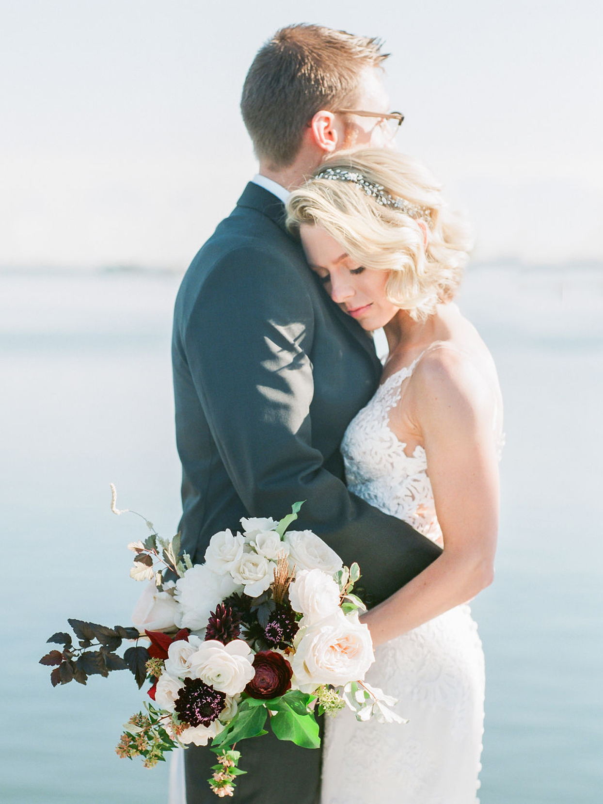 groom and bride embrace holding flower bouquet