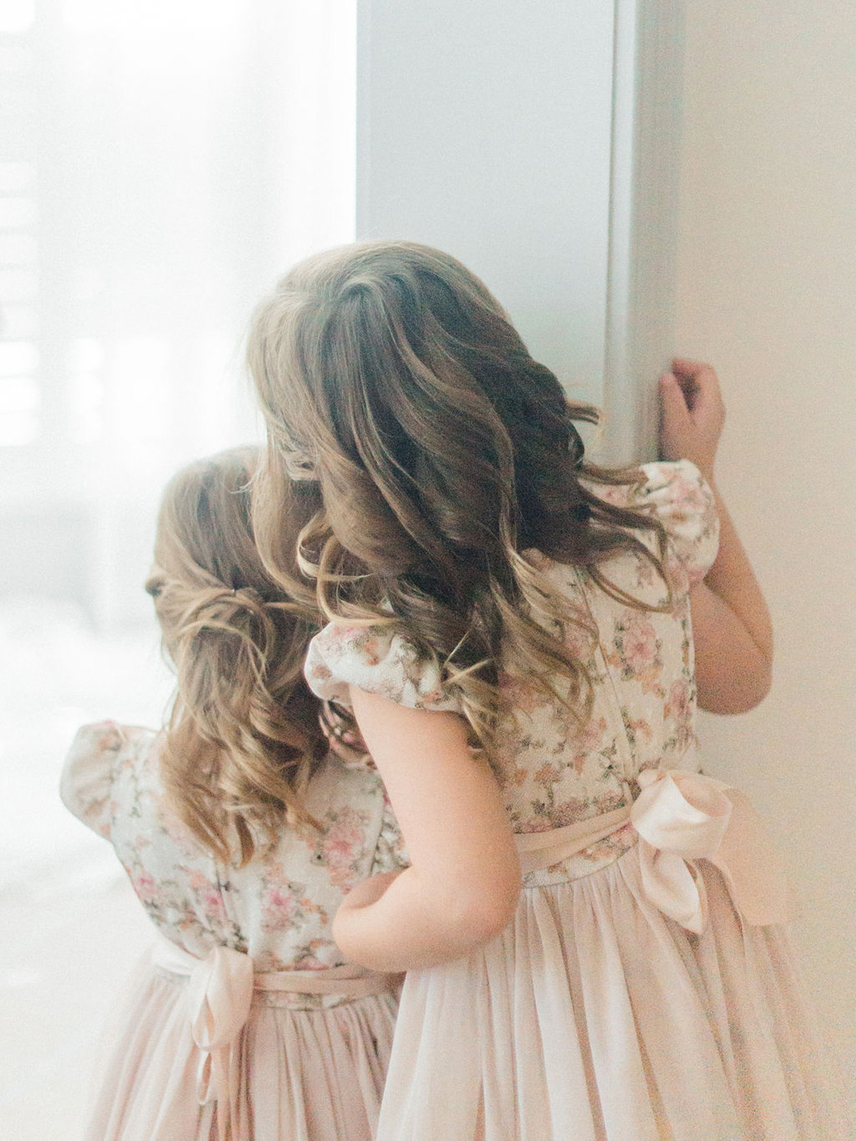 flower girls in pink floral dresses with satin bows