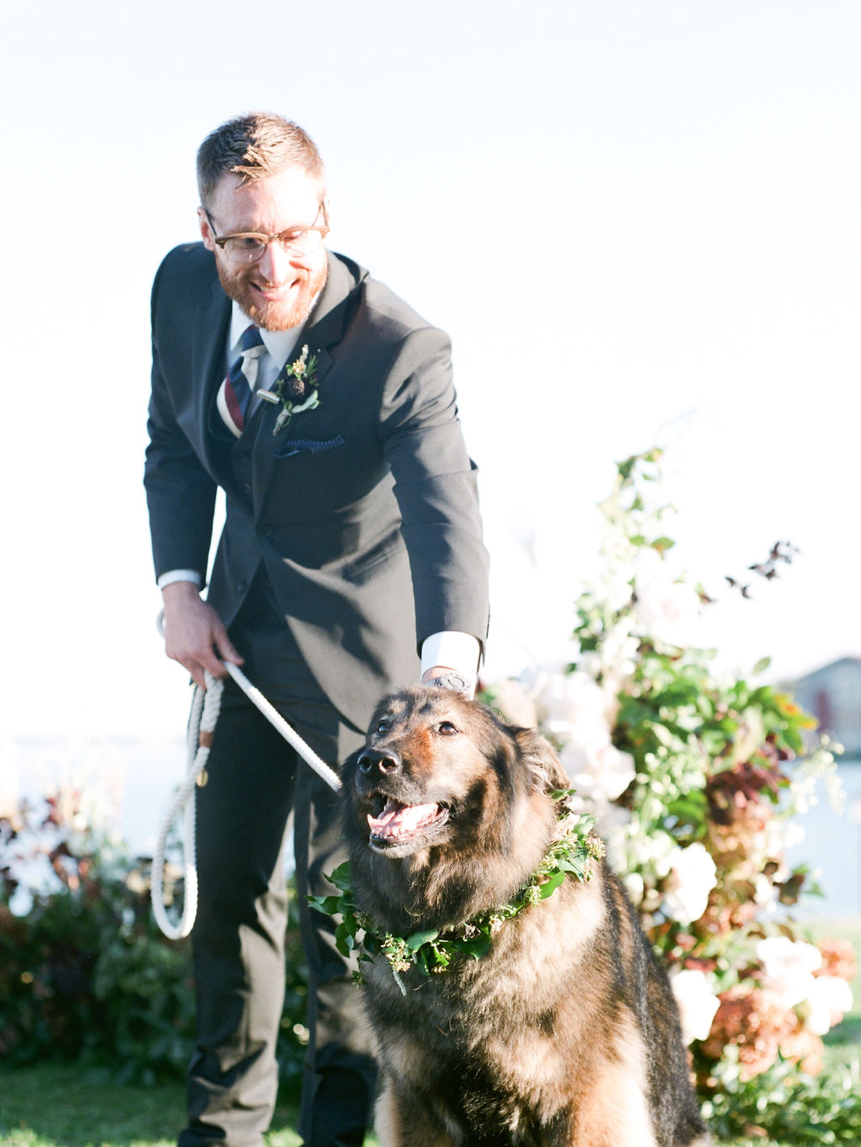 groom with dog wearing floral wreath